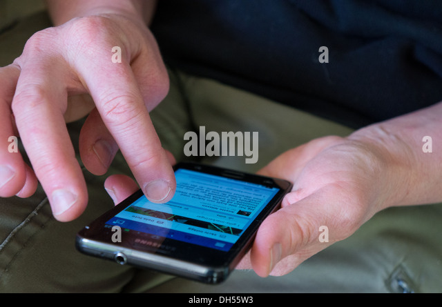 Facebook on a smart phone, hands - Stock Image