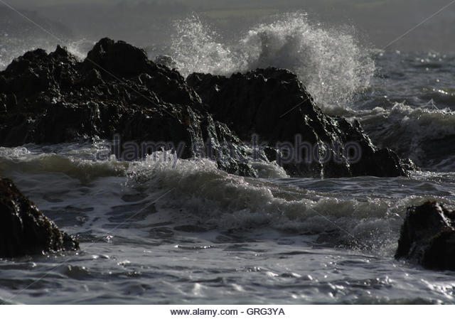 Storm waves smashing against rocks - Stock Image