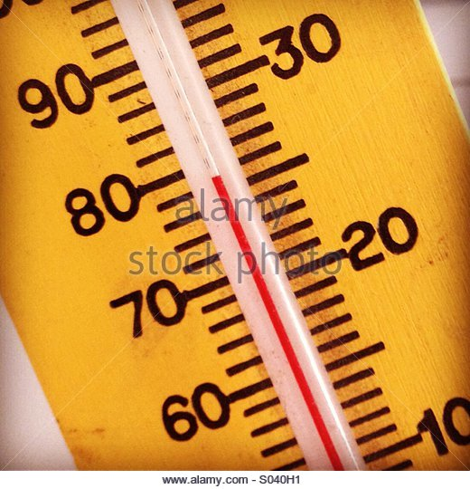 Thermometer showing a warm temperature in Fahrenheit and centigrade - Stock Image