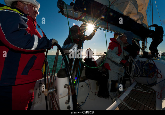 Captain at the wheel of ocean going yacht with crew working. - Stock-Bilder