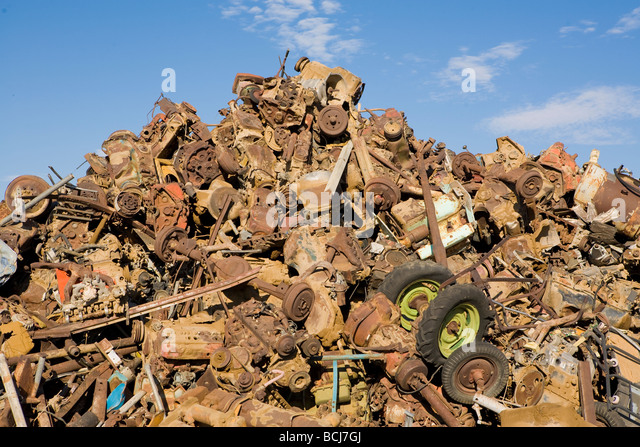 Stack pile of rusted metal car parts including wheels axles tires against sky Barstow California USA - Stock Image