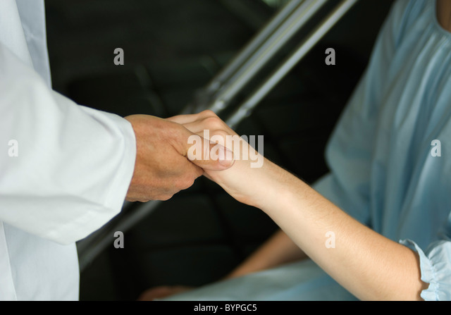 Doctor holding patient's hand - Stock Image