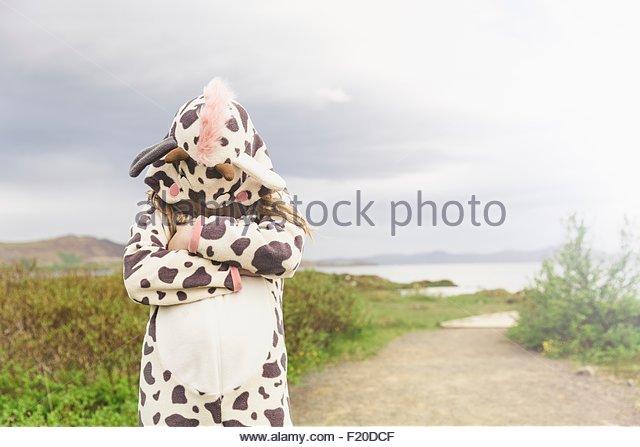 Girl wearing animal onesie hiding under hood, Thingvellir, Iceland - Stock Image