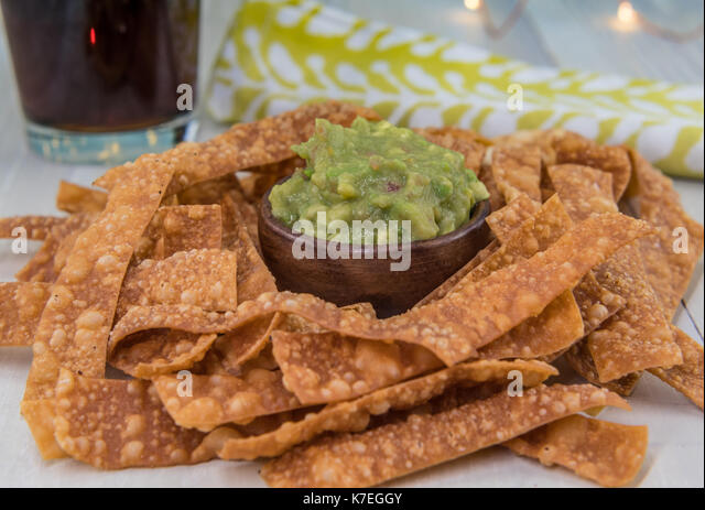 Bowl of Guacamole and Chips with Drink and Napkin in Background on light table top - Stock Image