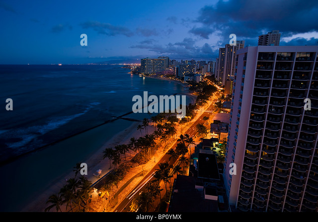 Early dawn light contrasts with ambient illumination from an awakening city of Honolulu, Hawaii, USA. - Stock Image