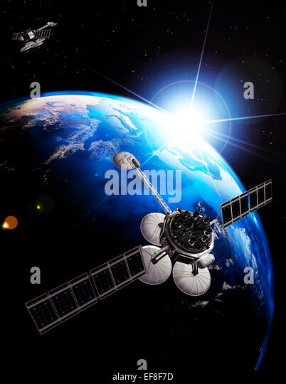Communication satellites above Earth lit by the rising Sun. Space internet and telecommunications concept. Photorealistic - Stock Image