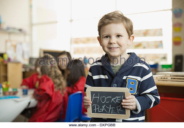Elementary boy holding slate with 'Hockey Player' written on it - Stock Image