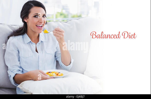 Balanced diet against happy woman sitting on the sofa eating fruit salad - Stock Image