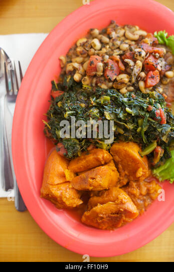 A healthy meal of vegan soul food, black eyed peas, greens and sweet potatoes served on a bright salmon pink plate, - Stock Image