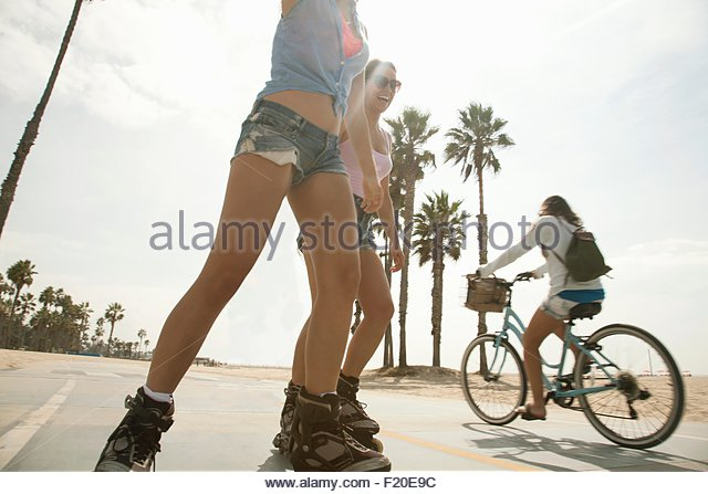 Young women rollerblading and cycling - Stock Image