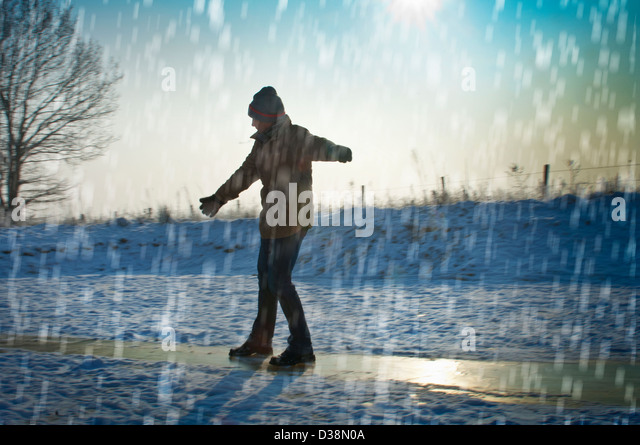 Man playing in snow - Stock Image