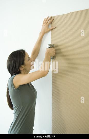Woman stapling sheet of cardboard to wall - Stock Image