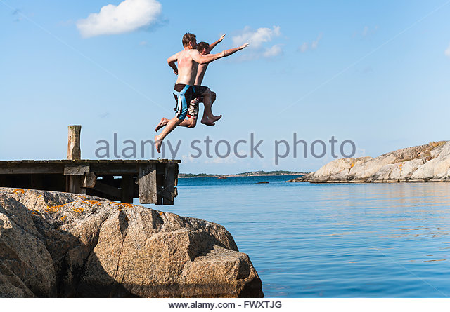 Sweden, Stockholm archipelago, Uppland, Vidinge, Two men jumping into lake from jetty - Stock-Bilder