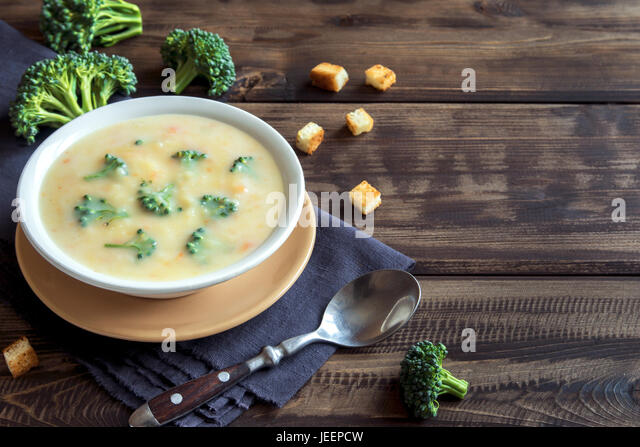 Vegetable and cheese cream soup with broccoli and croutons over wooden background with copy space - homemade healthy - Stock Image