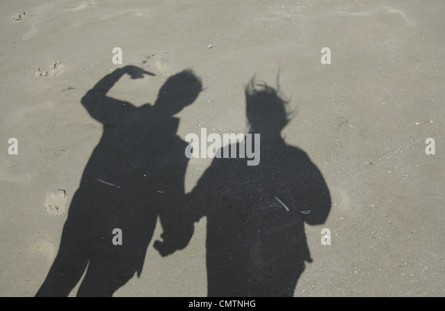 Shadow of couple on sand at beach - Stock Image