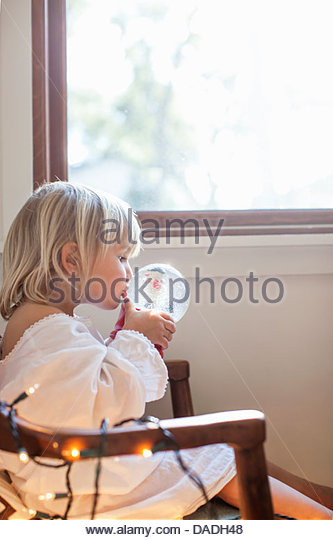 Girl kissing snow globe - Stock Image