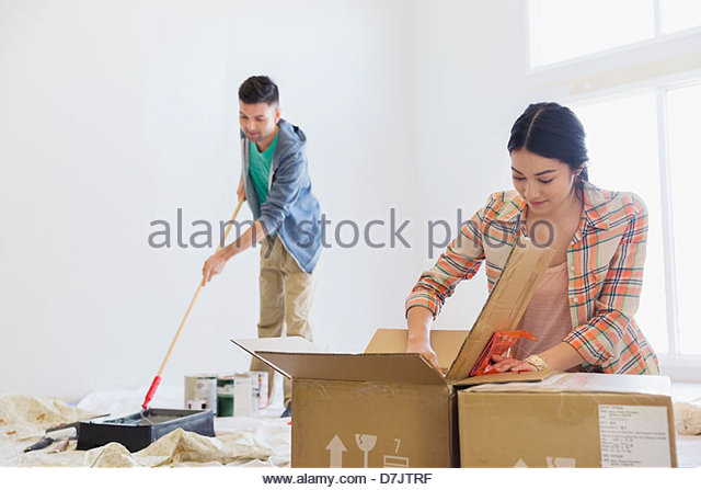Young couple painting and unpacking at home - Stock Image
