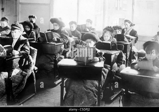 Children reading at desks in room of open air school, Providence - Stock Image