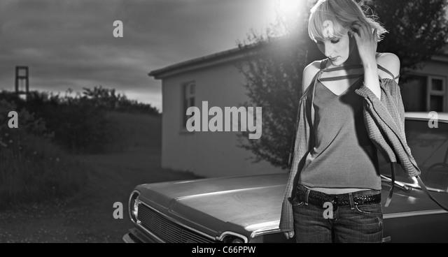Woman standing by vintage car - Stock-Bilder