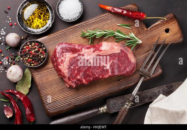 Raw ribeye beef steak cooking with ingredients. Top view - Stock Image