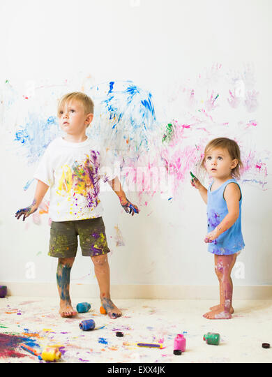 Children (2-3) painting on wall - Stock Image