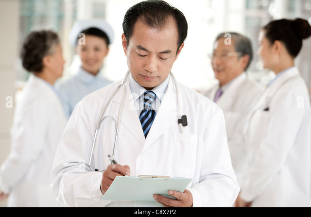 Doctor in Forground with Clipboard, Doctors and a Nurse in Background - Stock Image