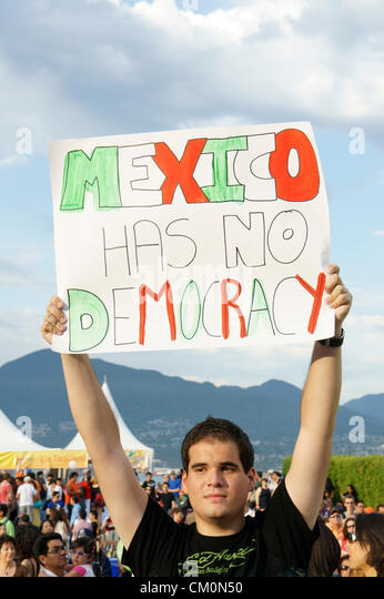 Young Mexican political protester holding up a sign at the Mexico Fest Mexican independence day celebrations in - Stock Image
