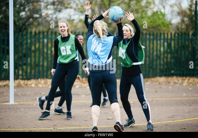 Female netball teams playing match on netball court - Stock Image