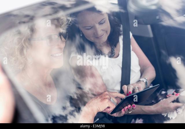 Senior women using digital tablet in car - Stock Image