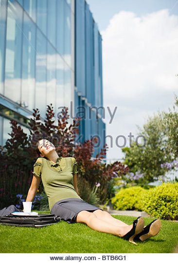 Smiling businesswoman sitting in grass and basking in sunlight outside office building - Stock Image
