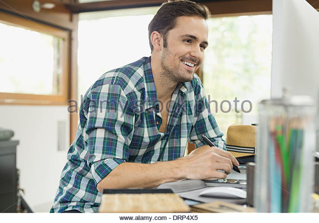 Working professional using digital drawing tablet - Stock Image
