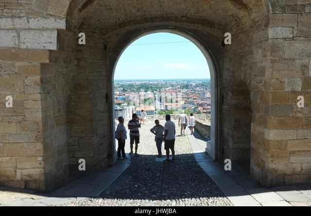 Tourists at the Porta San Giacomo gate, facing towards the lower city from the Citta Alta (upper city), Bergamo, - Stock Image