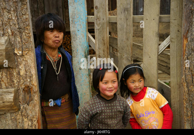 Mother with two girls at gate to framhouse, Phobjikha valley, Bhutan - Stock Image