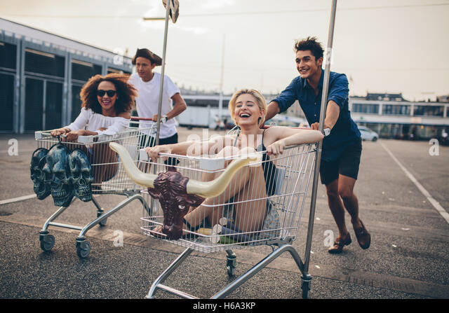 Young people racing with shopping trolleys on road. Multiracial group of friends racing with shopping cart. - Stock Image