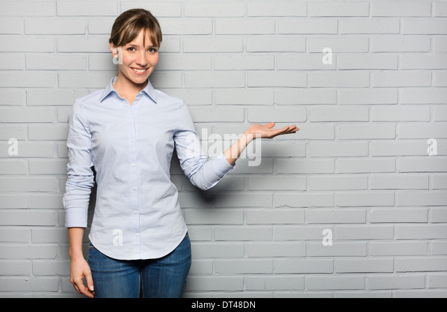 Female pretty cheerful pointing studio grey background - Stock Image