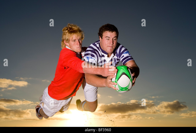 Rugby Tackle at Sunset. - Stock Image