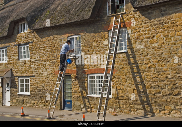 Decorator painting thatched cottage, Abbotsbury, Dorset, UK. - Stock-Bilder