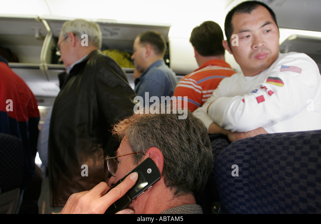 New Jersey Newark Airport Continental Flight 44 from Miami overhead luggage storage carry on cell phone - Stock Image