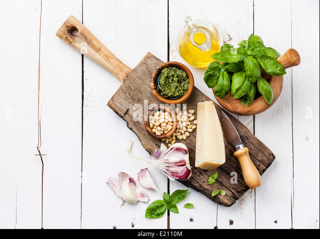 Ingredients for Preparing pesto in mortar on white wooden background - Stock Image