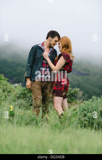 Romantic Couple Standing in Foggy Field - Stock Image