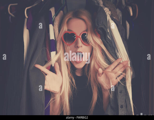 A woman is overwhelmed in a closet of messy clothes with red glasses for a style or fashion concept. - Stock Image