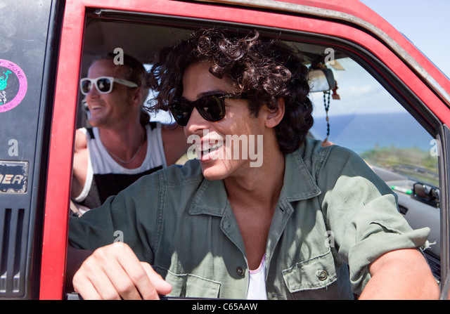 Two men looking out of open car window on vacation - Stock Image