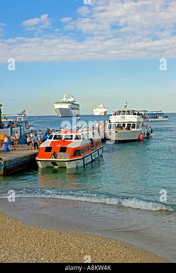 Grand Cayman George Town Harbor cruise ship passengers arrive in tender boats - Stock Image