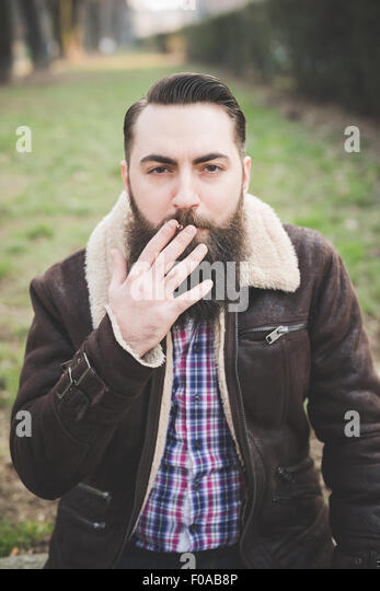 Young bearded man in park, Milan, Italy - Stock Image