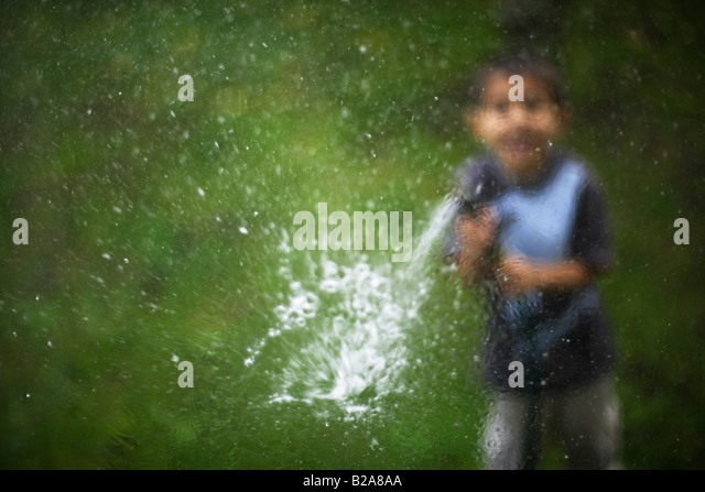Hosepipe sprayed at a glass window Six year old boy Mixed race indian ethnic caucasian - Stock Image
