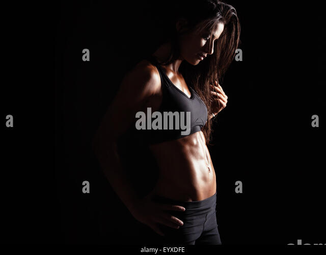 Image of female in sports clothing relaxing after workout on black background. Muscular female body with sweat. - Stock Image