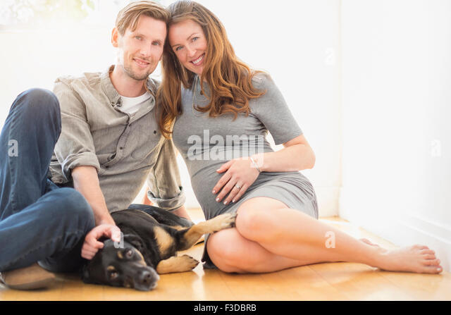 Portrait of mid-adult couple with dog indoors - Stock Image