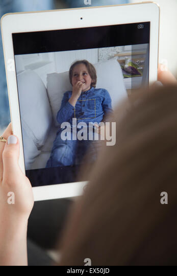Girl Taking Photo of her Brother with Digital Tablet - Stock Image