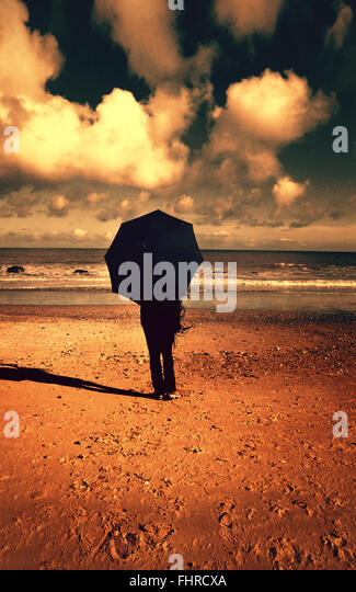 woman with umbrella on the beach - Stock Image