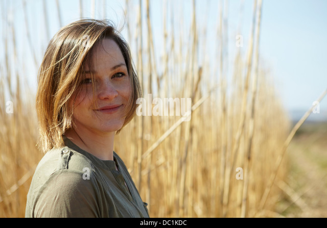 Portrait of young woman in front of reeds - Stock Image